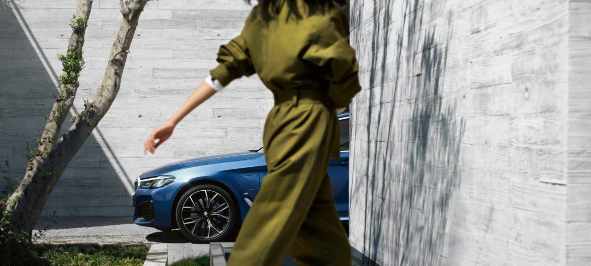 Frau geht vor BMW 5er Limousine eDrive (G30 LZI) - 530e