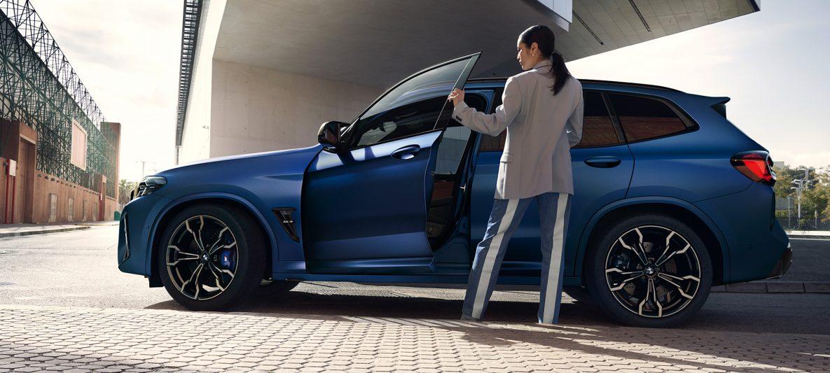 BMW X3 M Competition F97 LCI Facelift 2021 Frozen Marina Bay Blau metallic Seitenansicht mit geöffneter Tür und weiblichem Model